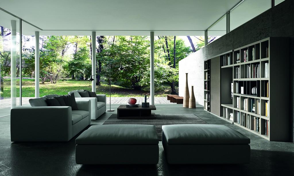 Soggiorno moderno luminoso con divani in pelle, pouff poggiapiedi e libreria porta tv